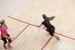 Two female squash players in fast action on a squash court Royalty Free Stock Images