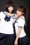 Two female students. Two Asian female students in traditional uniform posing on dark background Stock Images