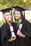 Two Female Students Attending Graduation Ceremony Stock Image