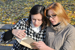 Two female students in the autumn  park. Two female students resting in the autumn  park , in series Stock Image