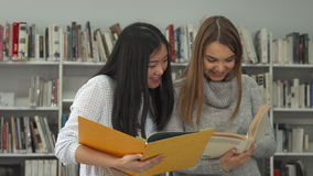 Two female students compare information in two books at the library. Two attractive female students comparing information in two books at the library. Brunette stock video