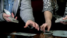 Two female students counting the money. Girls hold one dollar bills and count them stock footage