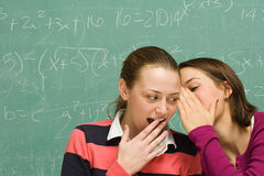 Two female students sharing a secret Royalty Free Stock Photos