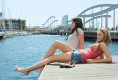 Two female students in shorts sittng on the berth Royalty Free Stock Photo