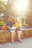Two female students sit at fountain and looking at laptop. Royalty Free Stock Images