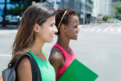 Two female students walking in the city in the summer. Two female students walking outdoor in the city in the summer Stock Photos