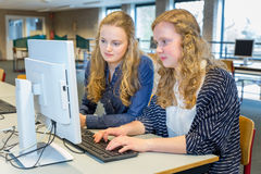 Two female students working together on computer in classroom Royalty Free Stock Photography