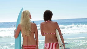 Two female surfers with boards at the beach. Looking at the water stock footage