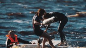 Two female surfers fighting with soft bats on surfing board in wavy water. Two caucasian female surfers in swimming suits fighting with soft bats standing on stock footage