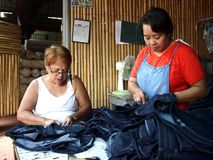 Two female tailors work on denim pants Royalty Free Stock Photography