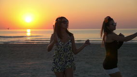 Two female teenagers on the beach with firework candles in their hands at sunrise. Two beautiful female teenagers on the beach with firework candles in their stock video