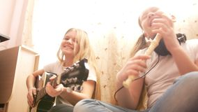 Two female teens playing musical instruments, guitar and flute, sitting on the floor at home