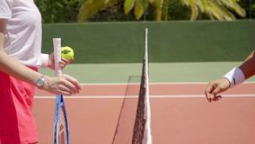 Two female tennis opponents shaking hands. Over the net at the end of a game of tennis in thanks and congratulations to the winner  close up of their hands stock video footage