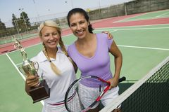 Two female Tennis Players by net on court holding trophy portrait stock photo