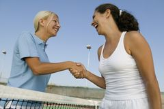 Two female Tennis Players shaking hand over tennis court net low angle view Stock Photos