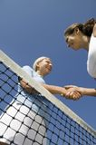 Two female Tennis Players shaking hand over tennis court net low angle view Royalty Free Stock Image