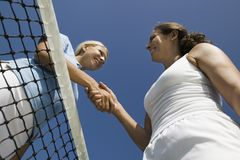 Two female Tennis Players shaking hand over tennis court net low angle view Royalty Free Stock Images