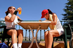 Two female tennis players sharing a joke after a game. Enjoying a glass of orange juice in the sun. Two fit, tanned female tennis players sharing a joke after a Royalty Free Stock Photos