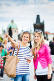 Two female tourists walking along the Charles Bridge Royalty Free Stock Images