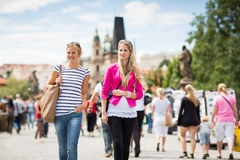 Two female tourists walking along the Charles Bridge Royalty Free Stock Photo