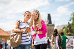 Two female tourists walking along the Charles Bridge Royalty Free Stock Photography