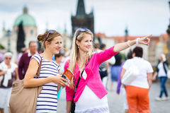 Two female tourists walking along the Charles Bridge Royalty Free Stock Photos