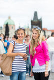 Two female tourists walking along the Charles Bridge. While sightseeing in Prague, the historical capital of the Czech Republic Stock Photography
