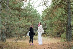 Two female tourists walking in the forest Stock Photos