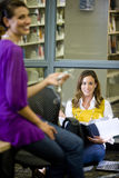 Two female university students talking in library. Two female university students conversing and listening to music in library royalty free stock photos