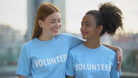 Two female volunteers smiling on camera, high school charity program, altruism stock video