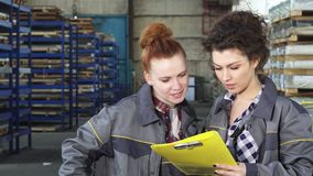 Two female warehouse workers examining documents together. Two beautiful young female warehouse workers doing paperwork working at the factory. Attractive young stock footage