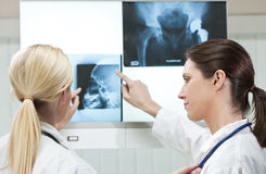Two Female Women Hospital Doctors with X-Rays. Two female women medical doctors looking at x-rays in a hospital Stock Image