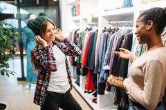 Two females buying clothes in shop, shopping. Shopaholics in clothing store, consumerism lifestyle, fashion stock photos