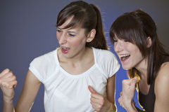 Two females cheer. By watching television - shot in studio stock photo