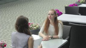 Two females discussing with each other in the cafe. Shooting from the back of brunette girl. Two beautiful young women sitting in outdoor cafe near the business stock footage