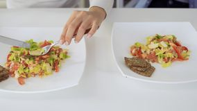 Two females eats salad. Women uses forks and knifes. Close-up. ProRes codec stock video footage