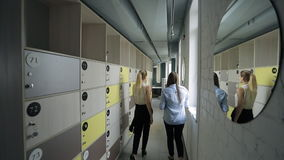 Two females are entering office corridor with clothes box. stock video footage