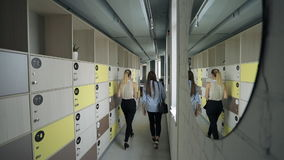 Two females are entering office hall with clothes box. stock video footage