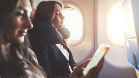 Two females going on business trip by plane. A woman reading an e-book on a smartphone. Two females going on business trip by plane. A women reading an e-book on stock photo