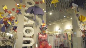 Two Females Mannequins in a Autumn Dress in a Modern Shop. Females mannequins in a slyling long autumn dress in a modern shop with defferent autumn paper stock footage
