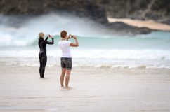 Two females taking photographs on a beach with mobile phones. Two females photograph surfers at a beach in Cornwall, England using mobile phones Stock Image