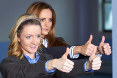 Two females shows thumb up gesture royalty free stock photography