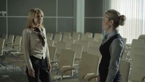 Two females talking in the conference hall of the airport. The action takes place in the conference hall of the airport. Two young pretty female have a small stock footage
