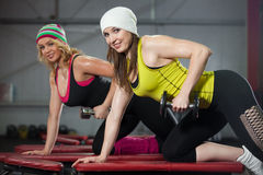 Two females train in gym with dumbbells Stock Photography