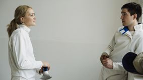 Two young fencers man and woman chatting after fencing tournament indoors Royalty Free Stock Photos