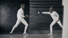 Two fencers man and woman have fencing match indoors. Two fencers men and women have fencing competition indoors Royalty Free Stock Photography