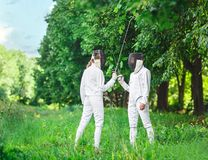 Two fencers women staying in park with crossed rapiers Royalty Free Stock Images