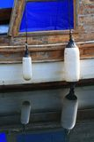 Two fender on an old boat with reflection in water. Two fender on an old wooden boat with reflection in water Stock Photo
