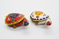 Two feng-shui colored metal turtles with detachable carapace shell for jewelry depositing on white background. Two feng-shui colored metal turtles with stock images