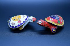 Two feng-shui colored metal turtles with detachable carapace shell for jewelry depositing on dark background royalty free stock images